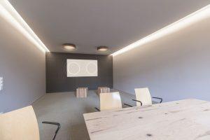 Konferenzraum mit Beamerleinwand und integrierten Lautsprecher von Hommbru